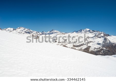 Stunning view of high mountain peaks in the italian alpine arc, in a bright sunny day of winter. Candid snowy slope in the foreground. - stock photo