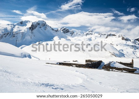 Stunning view of high mountain peaks in the italian alpine arc, in a bright sunny day. Ski resort of La Thuile and La Rosiere, on the border Italy France. Ruined mountain huts in the foreground. - stock photo