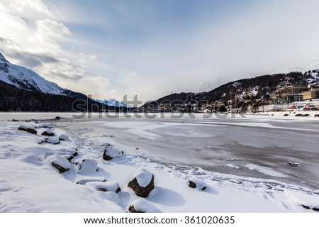 Stunning view of the icy St. Moritz lake and the city on the mountain in Winter, Canton of Grisons, Switzerland - stock photo