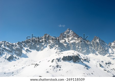 Stunning view on the majestic M. Viso (3841 m) arising from the snowcapped alpine arc in a bright sunny day of spring season with clear blue sky. Po Valley, Piedmont, Italy. - stock photo