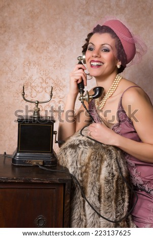 Stunning vintage 1920s woman talking on an antique telephone - stock photo