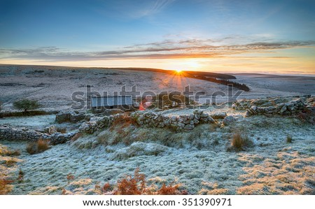 Stunning winter sunrise on a frosty morning over and old stone barn on remote moorland - stock photo