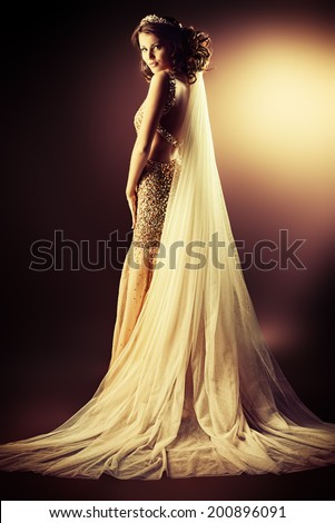 Stunning woman in luxurious golden dress and a veil posing over dark background. - stock photo