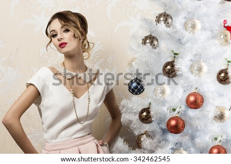 stunning woman with aristocratic elegant style near christmas decorated tree with hair-style, cute make-up and pearl necklace. xmas fashion holidays  - stock photo