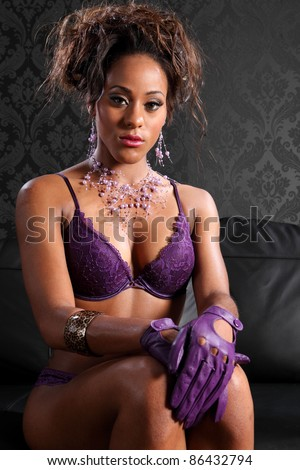 Stunning young african american glamour model woman wearing sexy purple lace lingerie and leather gloves, sitting on black leather sofa. Model has fashion necklace and bracelet on. - stock photo