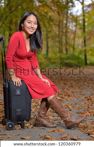 Stunning young Asian woman in red dress and boots sitting on a small black suitcase on the side of a leaf covered road - autumn travel