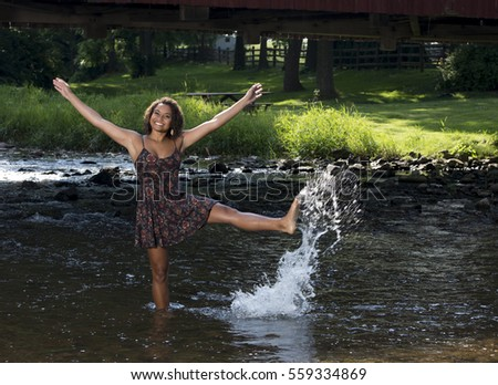 Stunning young biracial woman in dark print sundress standing in shallow creek - rural summer - kicking and splashing in water