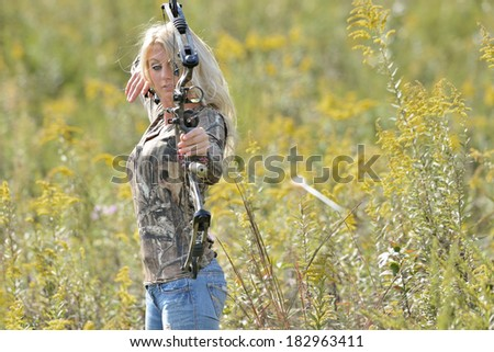 Stunning young blonde archer (female) shooting a bow in a camouflage top - arrow in frame leaving bow - stock photo