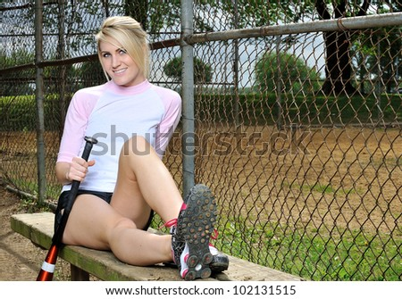 Stunning young blonde female softball player relaxes on bench holding bat in pink baseball shirt - stock photo