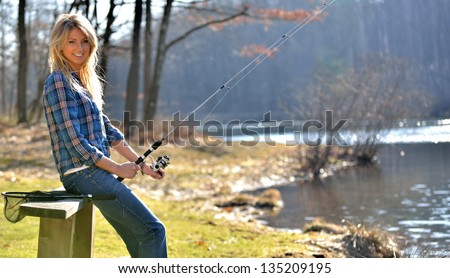 Stunning young blonde woman blue flannel shirt sitting on a bench by a pond fishing