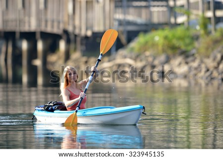 Stunning young blonde woman rows in her kayak on a lake as sun rises behind her