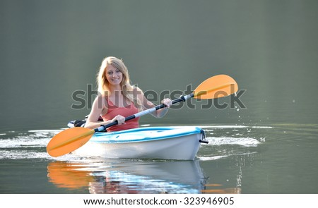 Stunning young blonde woman rows in her kayak on a lake as sun rises behind her - stock photo
