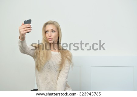 Stunning young blonde woman takes a selfie with her cell phone - stock photo
