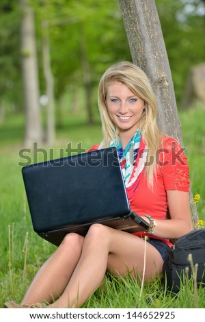 Stunning young blonde woman using her laptop computer while sitting in green grass of a college campus - student or education stock