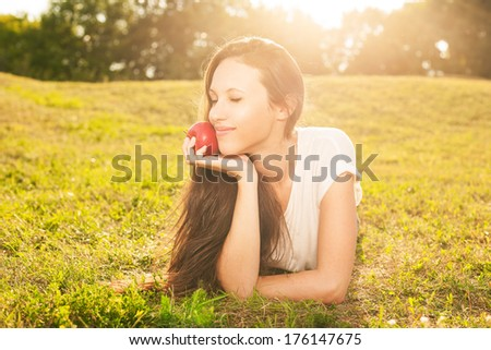 Stunning young brunette eating apple lying on grass in sunshine