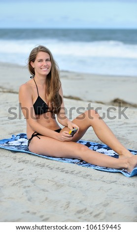 Stunning young Caucasian woman laying on blue beach blanket wearing a black bikini - smiling as she texts on her cell phone