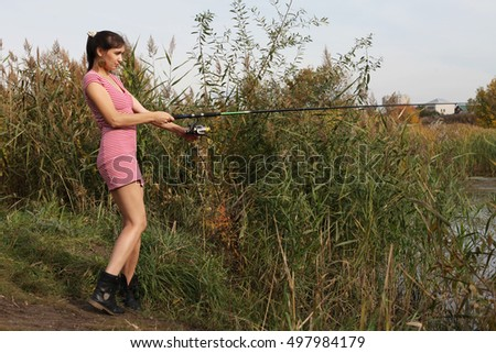 Stunning young girl in a red dress on a fishing trip
