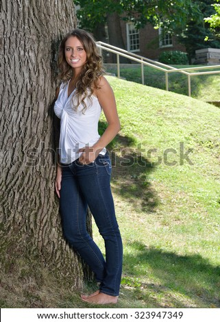 Stunning young Hispanic woman in white tank top and blue jeans - casual fashion - posing in park next to tree - stock photo