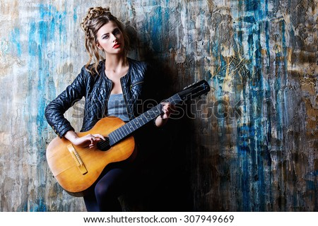 Stunning young woman in black leather jacket standing with her guitar by a grunge wall. Rock style, rock music. Fashion shot. - stock photo