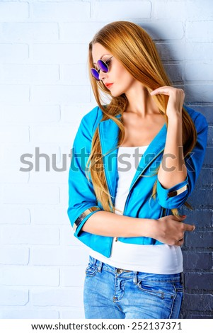 Stunning young woman posing by the white brick wall. Jeans style. Beauty, fashion. - stock photo