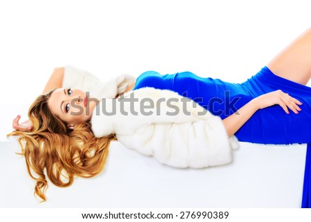 Stunning young woman posing in fashionable dress and mink fur jacket. Luxury, rich lifestyle. Fashion shot. Isolated over white background. - stock photo