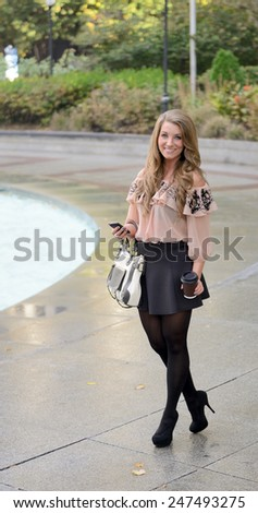 Stunning young woman standing in city park wearing black skirt and salmon colored blouse holding smart phone, coffee cup, and purse - stock photo