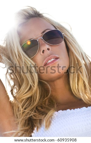 Stunningly beautiful young blond woman in a white dress and aviator sunglasses backlit by sunshine
