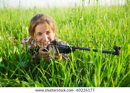 stunningly beautiful young woman   with air rifle in grass
