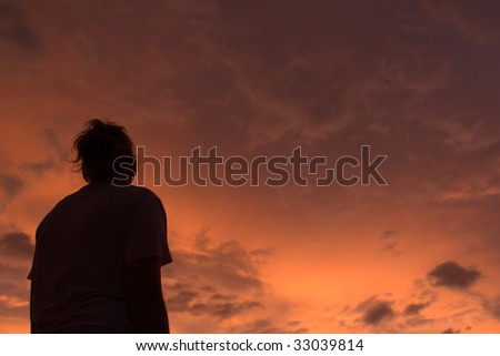 Stunningly beautifully colored sunset with the silhouette of a young woman observing. - stock photo