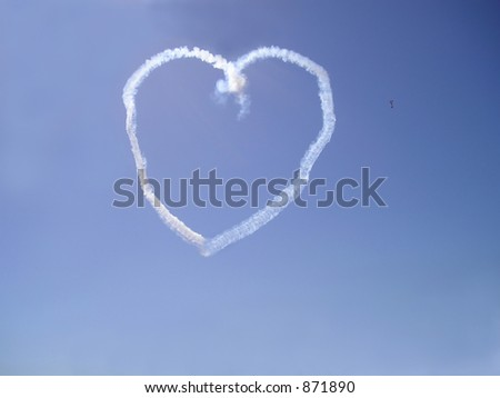 Stunt airplane making heart figure in the sky - stock photo