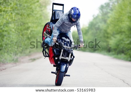 Stunt rider making stoppie on the summer forest background - stock photo