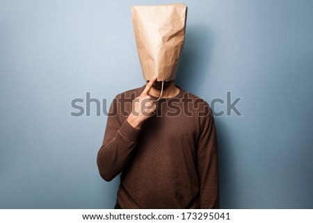 Stupid young man with bag over his head - stock photo