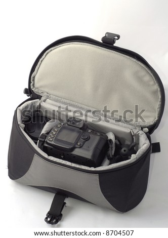 Sturdy backpack for carrying a camera and related equipment safely open showing the camera and lens - stock photo