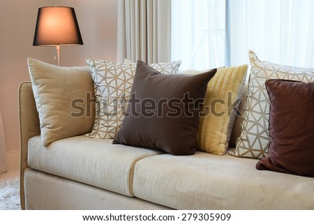 Sturdy brown tweed sofa with brown patterned pillows and lamp - stock photo