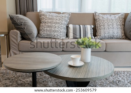 Sturdy brown tweed sofa with grey patterned pillows - stock photo