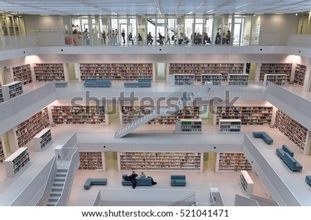 Stuttgart, Germany - April 16, 2015: Interior of modern library in Stuttgart. White floors with bookshelves connected with stairs and visitors.