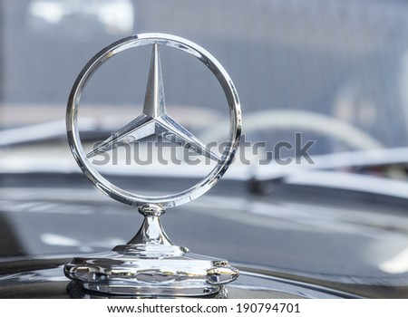 STUTTGART,GERMANY- AUG 11:Mercedes logo on a traditional car in front of an elegant hotel in Stuttgart,Germany on August 11, 2013.In Stuttgart is the headquarter of Mercedens-Benz. - stock photo