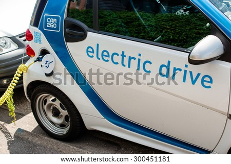 STUTTGART, GERMANY - JULY 25, 2015: An electric Smart of car sharing company car2go is being plugged into a charging station in Stuttgart, Germany. Car2go is a company of the Daimler group  - stock photo