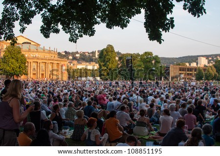 STUTTGART, GERMANY - JULY 25: More than 5.000 people are watching the public viewing of the premiere of Mozarts opera Don Giovanni on a large screen in front of the Opera building in Stuttgart. - stock photo