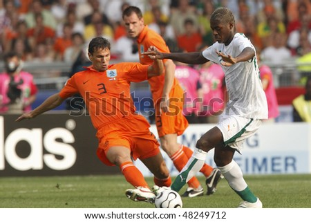 STUTTGART, GERMANY - JUNE 16:  Khalid Boulahrouz of Holland (l) tackles Romaric of Cote d'Ivoire during a World Cup  match June 16, 2006 in Stuttgart, Germany. Editorial only.  No mobile device usage. - stock photo