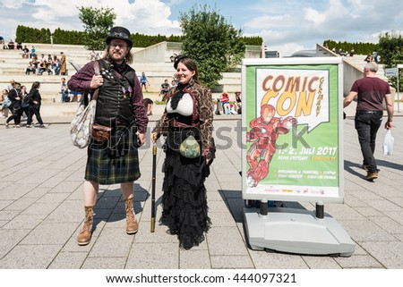 Stuttgart, Germany - June 25, 2016: Two cosplayers are posing during the Comic Con Germany event in Stuttgart in front of the exhibition hall on public ground next to the poster announcing next year