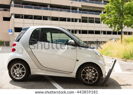Stuttgart, Germany - June 25, 2016: Very bad parked small Smart car, hitting a metal blocker while parking illegally in a blocked space in front of a multi storey parking garage at the airport in - stock photo