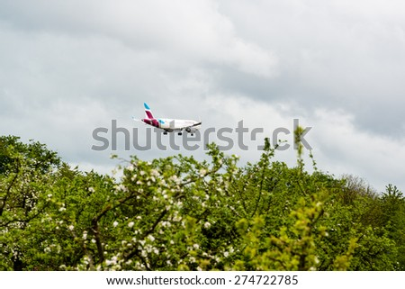 STUTTGART, GERMANY- MAY 03, 2015: A Eurowings airplane is approaching Stuttgart Airport in Germany.Eurowings is a fully owned subsidiary of the Lufthansa Group, offering low-cost flights throughout - stock photo