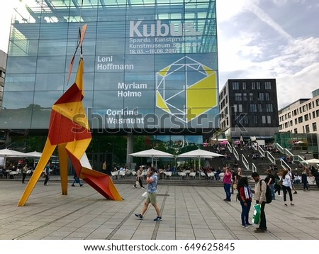 Stuttgart, Germany - May 24, 2017: The Museum of Art in Stuttgart Germany is promoting its latest exhibitions on its modern cubic glass facade.