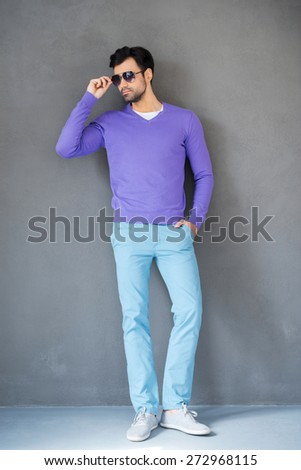 Style is everything. Full length of handsome young man adjusting sunglasses and looking away while standing against grey background  - stock photo