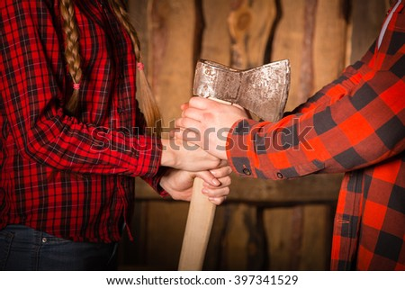 Style lumberjack. Man and girl in red checkered shirt holding ax. Woodcutter - stock photo