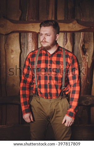 Style lumberjack. Woodcutter with a beard and mustache, wearing a red shirt, pants and suspenders with an ax on a wooden background. Modern style. Thoughtful lumberjack - stock photo