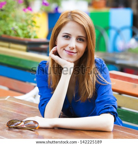 Style redhead girl sitting on the bench in the cafe