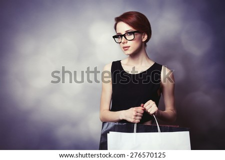 Style redhead girl with glasses and black dress with shopping bags on grey background - stock photo