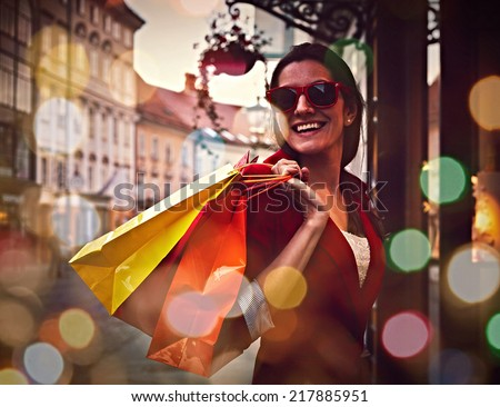 Style smiling girl with shopping bags near the store